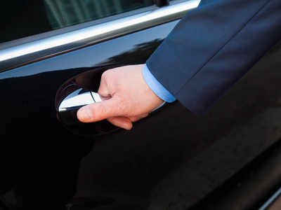 Chauffeur's hand opening passenger door